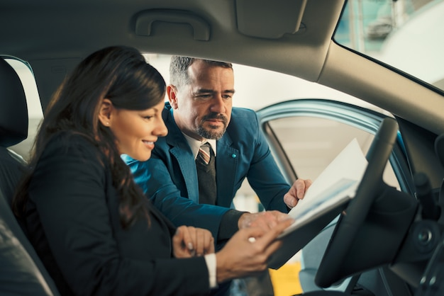 Car dealer showing businesswoman contract in car showroom.