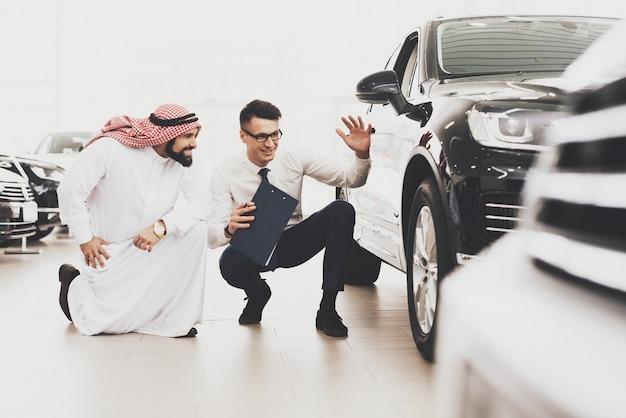 Car dealer showing car wheel to arab customer