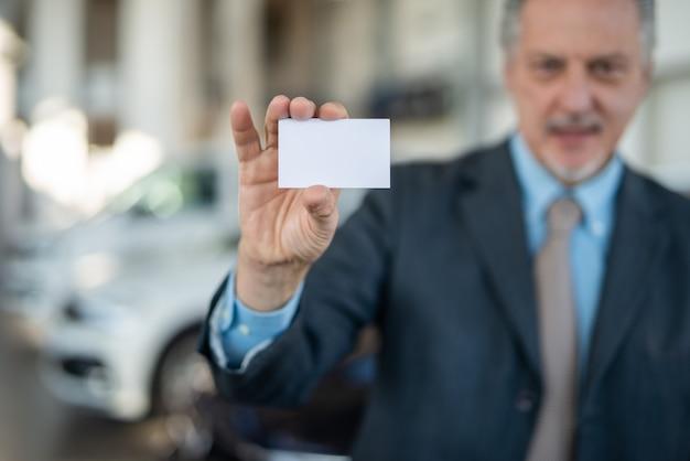 名刺を見せている自動車ディーラー