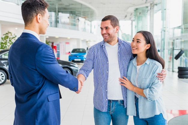 Car dealer talking to clients
