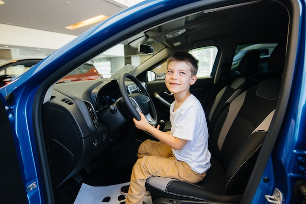 In a car dealership, a happy boy is driving a new car. car purchase.