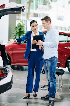 Car dealership manager showing big trunk of automobile to young customer