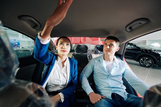 고객에게 자동차 구획에서 조명을 켜는 방법을 보여주는 자동차 대리점 관리자