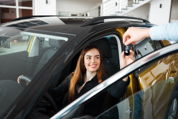 カーディーラーの売り手がクライアントに車のキーを渡します