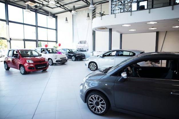 販売のための真新しい車を備えた自動車販売店のショールームのインテリア。
