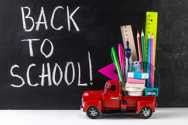 Car delivering school stationery against blackboard. education concept.