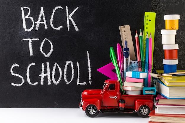 Car delivering school supplies against blackboard. education concept.