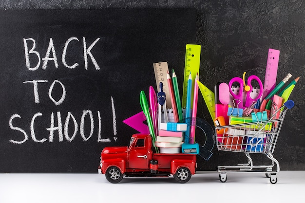 Car delivering shopping cart with accessories against blackboard.