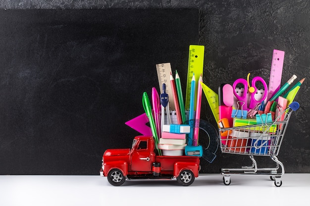 Car delivering shopping cart with accessories against blackboard
