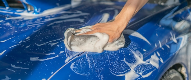 A car detailing, close up hand holding a sponge and cleaning the car