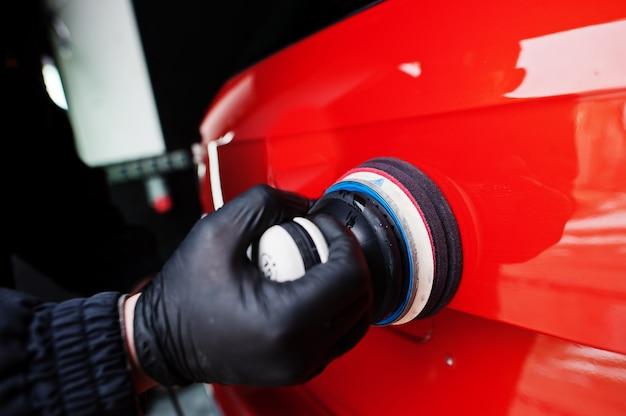 カーディテールコンセプト。オレンジ色のsuv車を磨く修理店で軌道研磨機を持つ男の手。
