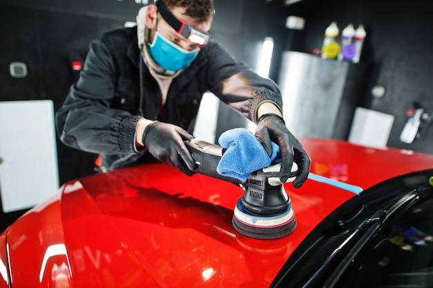 Концепция детализации автомобиля. человек в маске с орбитальным полировщиком в ремонтной мастерской, полируя оранжевый внедорожник.