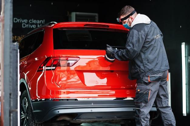 カーディテールコンセプト。オレンジ色のsuv車を磨く修理店でオービタルポリッシャーとフェイスマスクの男。