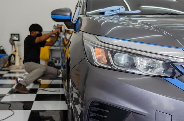 車の詳細-車の研磨機を保持している男性のメカニック。自動車産業、自動車の研磨、塗装、修理店。自動車のヘッドライトに焦点を当てる
