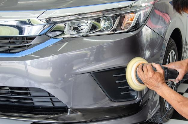 車の詳細-車の研磨機を保持している男性のメカニック。自動車産業、自動車研磨、塗装、修理店。