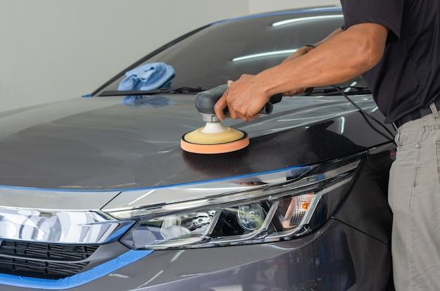 Детализация автомобиля - мужчина-механик, держащий машину для полировки автомобилей. автопром, автомастерская, полировка и покраска и ремонт.