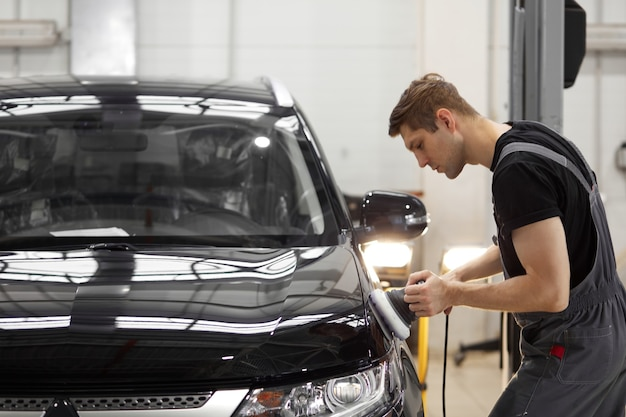Car detailing and polishing concept. young professional car service male worker