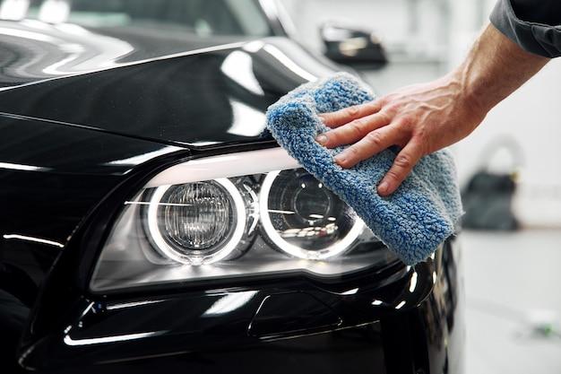 자동차 세부 사항-남자가 마이크로 화이버를 손에 들고 차를 닦습니다.