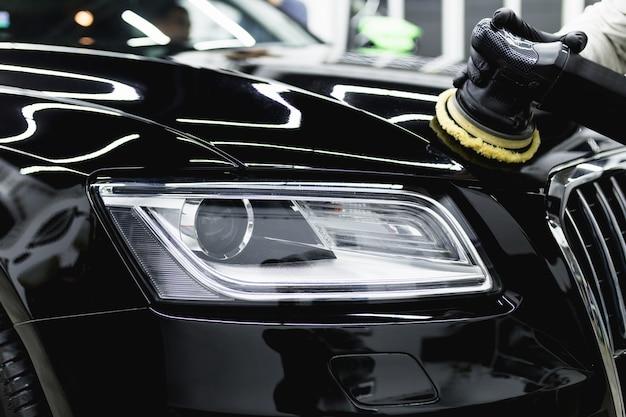 Детализация автомобиля - рабочий с орбитальным полировщиком в автомастерской.