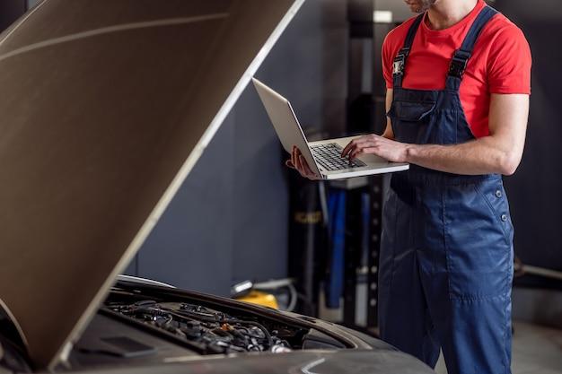 Авто, диагностика. руки автомеханика в синем комбинезоне, стоящего с ноутбуком возле открытого капота автомобиля в мастерской