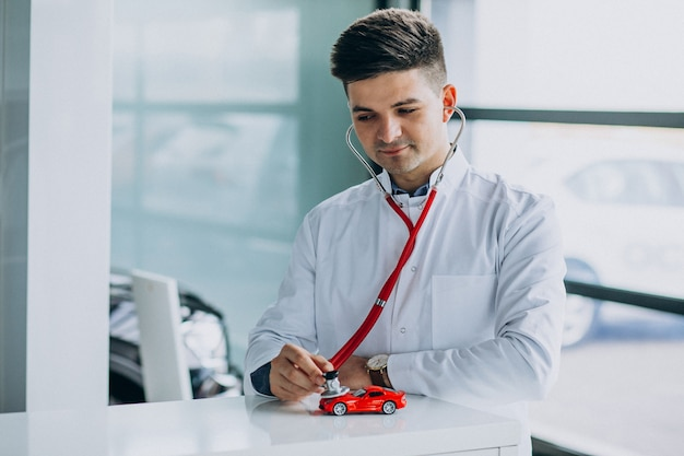 Car doctor with stethoscope in a car showroom