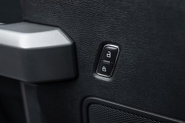 Кнопка разблокировки дверного замка автомобиля крупным планом кнопка электрического центрального замка в современном автомобиле выборочный фокус