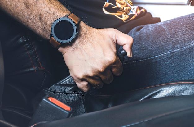 주차장에 있는 차에서 핸드브레이크 레버를 당기는 자동차 운전자