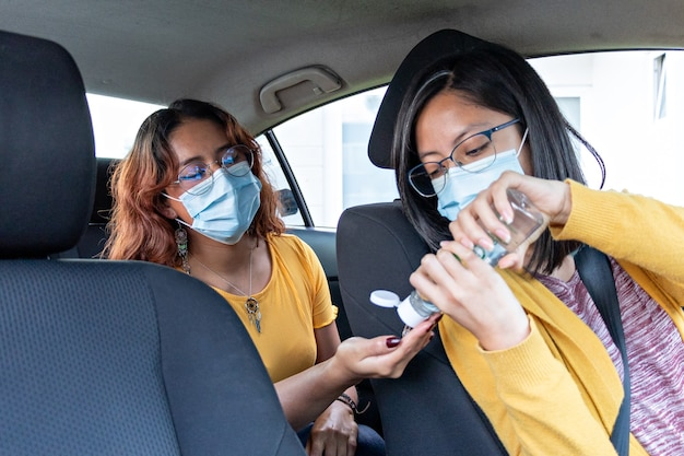 Car driver puts antibacterial gel on backseat passenger