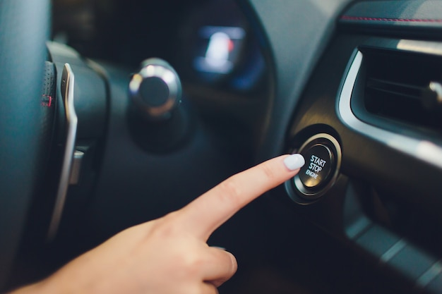 Car driver starting the engine keyless. black. female hand.