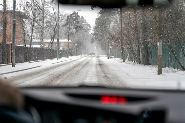 눈보라의 겨울 도로에서 자동차 운전. 내부보기. 앞 차가 눈이 드리프트