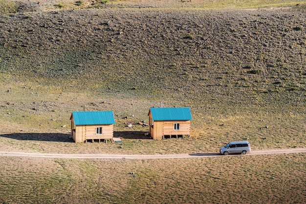 Car driving along field road past tourist houses chui steppe autumn in the altai mountains