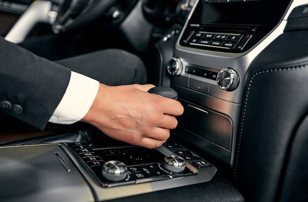 Концепция вождения автомобиля. водитель переходит в режим движения. рука на трансмиссии крупным планом
