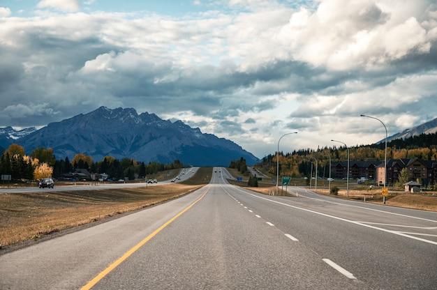 캐나다 캔모어에서 가을에 로키 산맥이 있는 고속도로에서 운전하는 자동차