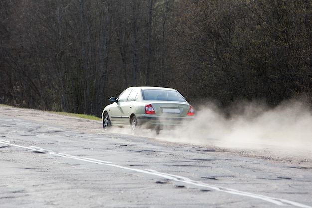 아스팔트의 움푹 들어간 곳을 피하기 위해 길가를 운전하는 자동차. 나쁜 고속도로 품질 문제 및 유지 보수