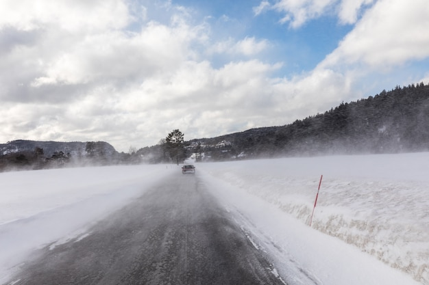 Car driving in winter blizzard on snowy road in norway