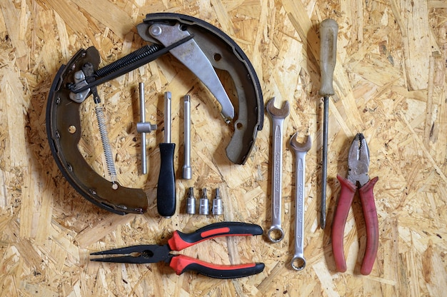 Car drum brake disassembled and a set of various repair hand tools or auto mechanic's tools kit on a sheet of osb plywood background. flat lay, top view