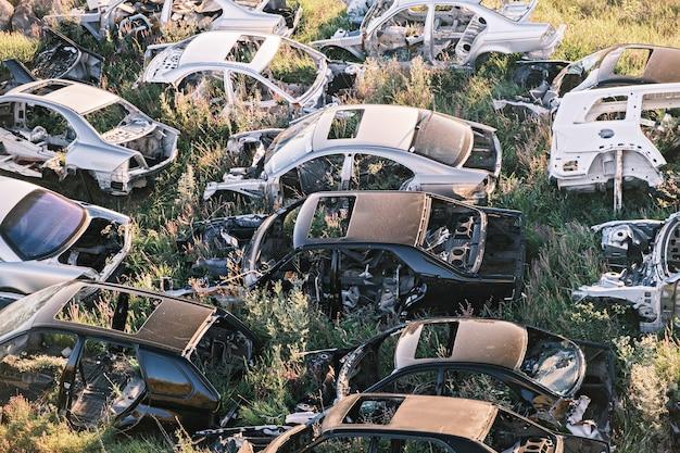 Автомобиль сбрасывает кучу старых гнилых сломанных машин в поле, вид сверху