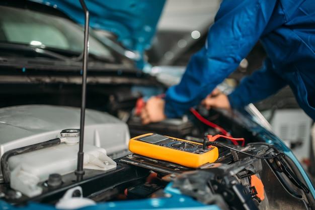 Автоэлектрик проверяет уровень заряда аккумулятора