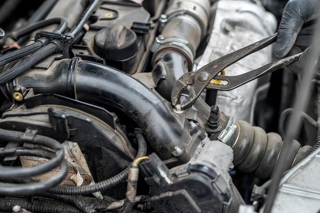 자동차 엔진, 수컷 손 및 도구 고정 너트 프리미엄 사진