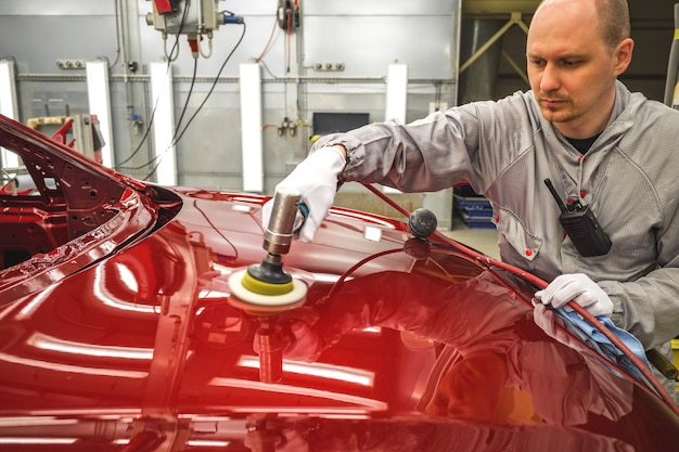 Car factory worker polishes painted surface