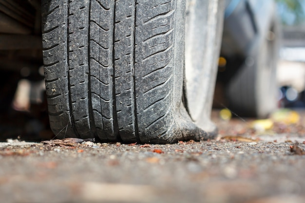 車のパンクしたタイヤが助けを待っています。