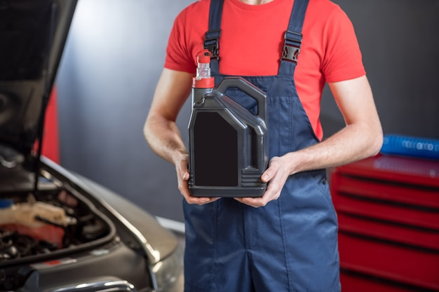 Car fluid. hands of car mechanic in overalls holding black canister in workshop, face is not visible