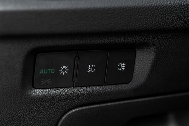 車のフォグランプスイッチがクローズアップ。コントロールスイッチパワーライトシステム。車のライトコントロールパネル