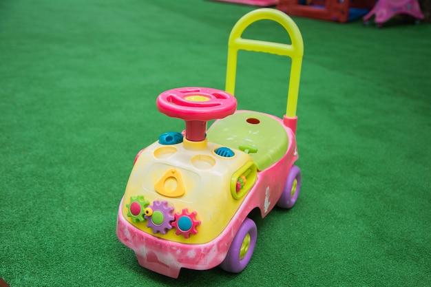 분홍색 스티어링 휠이 밝은 세부 사항과 승차용 핸들이 있는 어린이를 앉힐 수 있는 자동차