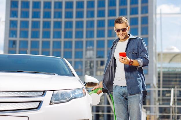 車の燃料。ガソリンスタンドにいる間彼の車に燃料を供給する自信のある前向きな男