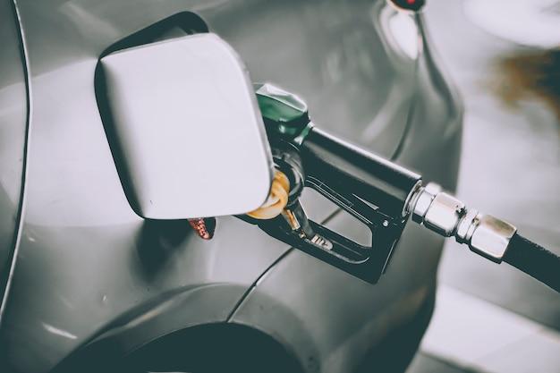 車のガスノズルの給油は、ガソリンスタンドでガソリンガソリンで満たされます。輸送と所有権の概念。ガソリンスタンドのコンセプトで車をいっぱいにします。