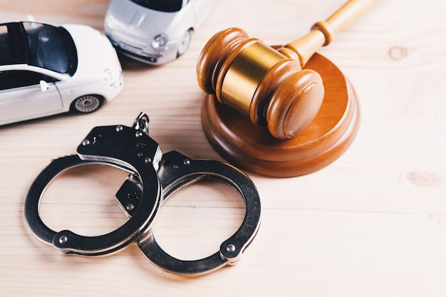 Car, handcuffs and a hammer. accident and lawsuit