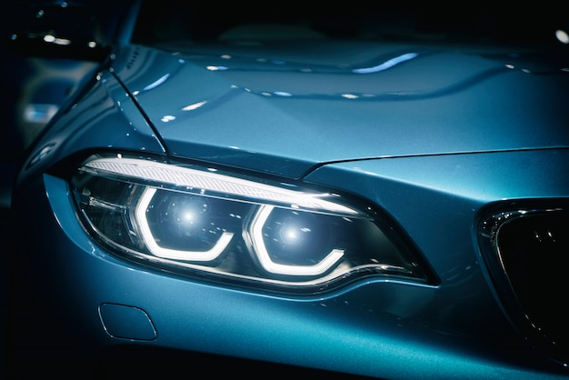 Car headlight and hood of powerful sports blue car with blue glare on dark background.