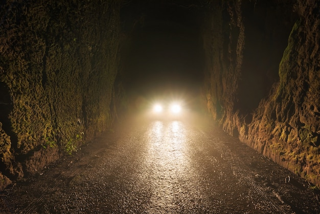 Car headlights at night in the foggy road