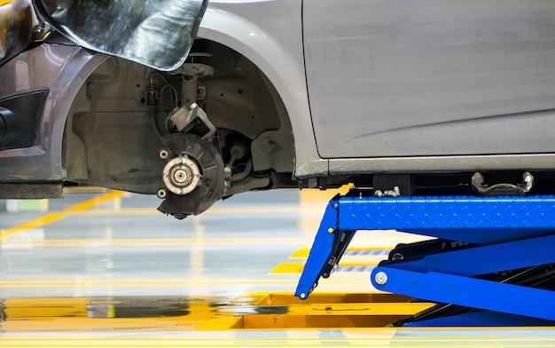 ガレージで青い車のハブフロントリフティングはさみ